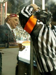 Volunteer goal judge Rufus Lopez (left) and referee Steve Cruickshank discuss the fate of Game 7 of the 2004 Presidents Cup Final.