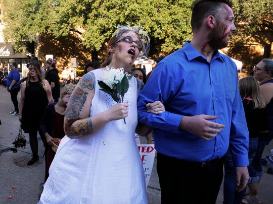 """Zombie-bride Liz Berry looks up to her Zombie-groom Darian Bittick after a fictional wedding during ArtWalk Thursday Oct. 12, 2017 which promoted """"Haunted Abilene"""" at the Swenson House. Halloween costumes, dance troops, and health emergency response teams were on display during this month's event called """"The Art of Response: Zombie Preparedness."""""""