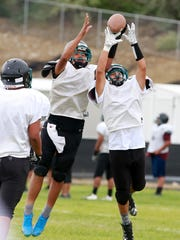 Navajo Prep sophomore Kasey James, left, and freshman Jesse Andis battle for a pass during practice on Tuesday at Navajo Prep.