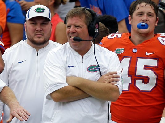 FILE - In this Sept. 30, 2017, file photo,Florida head coach Jim McElwain, center, watches play against Vanderbilt during the second half of an NCAA college football game in Gainesville, Fla. The Gators parted ways with McElwain and announced defensive coordinator Randy Shannon as their interim coach Sunday, Oct. 29, 2017. (AP Photo/John Raoux, File)