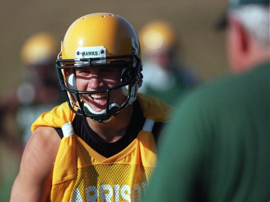 Farmington Hills Harrison quarterback Drew Stanton has a laugh with his teammates and coaches on the practice fields before the team's first official practice on the opening day of the 2001 season. Stanton went on to play at Michigan State and then in the NFL.