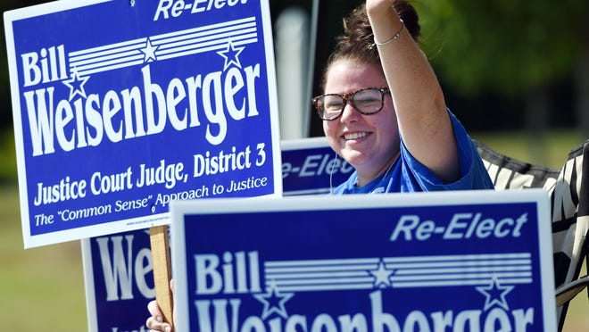 Lea McClain waves to motorists passing on Old Canton Road in Madison while showing her support for Justice Court Judge Bill Weisenberger near the precinct located at the old Victory Church.