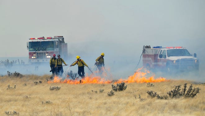 Firefighters battle flames in a brush fire that started in Prescott Valley on May 11, 2018. The fire, driven by a sustained wind, has burned several structures and closed a state highway.