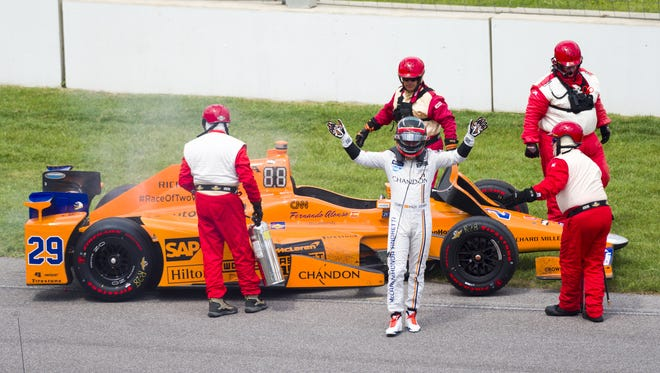 Fernando Alonso reacts to the crowd's applause after climbing from his car. Alonso's engine quit on him during the running of the 101st Indianapolis 500, at Indianapolis Motor Speedway, Sunday, May 28, 2017.