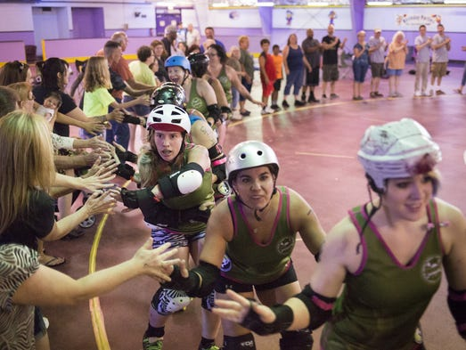 Members of the York City Derby Dames slap hands with