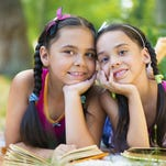 Portrait of two hispanic sisters reading in the park