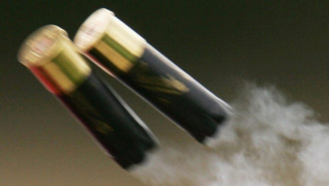 Empty shells eject from a shotgun during trap shooting.