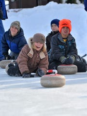 Claire Butalla, 10, of Wausau tries curling while her 9-year-old cousin Jake Pease of Marathon looks on at The 400 Block in downtown Wausau at 2014's Winter Fest.