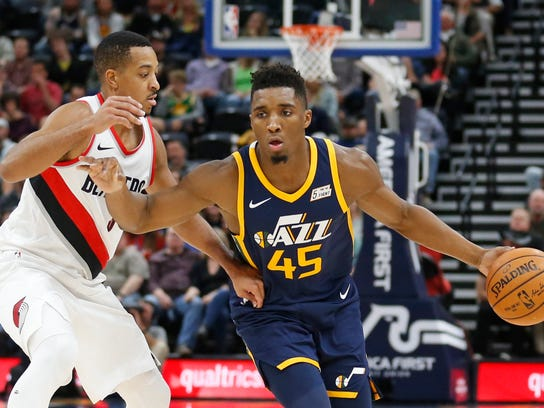 Portland Trail Blazers guard CJ McCollum, left, guards Utah Jazz guard Donovan Mitchell (45) as he drives in the first half during an NBA basketball game Wednesday, Nov. 1, 2017, in Salt Lake City. (AP Photo/Rick Bowmer)