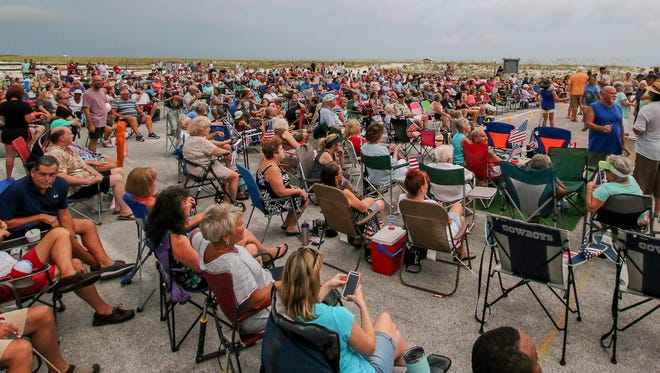Hundreds of people enjoy music by Emerald Gold on July 19 during the weekly Tunes by the Dunes concert series on Navarre Beach. The free summer concert series continues this week with the classic rock of Red Moon Travelers.