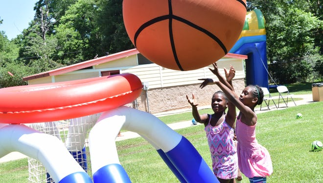 D'Asia Leache (left), 8, and her sister, D'Kia Leach, 9, throw a giant basketball into a hoop at Harmon Park during a visit by the city of Alexandria's Rec2U mobile recreation program. More than 2,000 youths took part in the Rec2U program this summer, Mayor Jacques Roy said in his State of the City speech in noting expanded recreational opportunities.