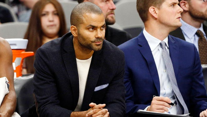 San Antonio Spurs point guard Tony Parker (left) watches from the bench during the second half against the Sacramento Kings at AT&T Center.