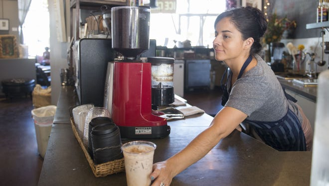 Bibi Canales serves a drink at Fair Trade Cafe in Phoenix in July. The coffee shop is a member of Arizonans for Fair Wages and Healthy Families, which supports Proposition 206.