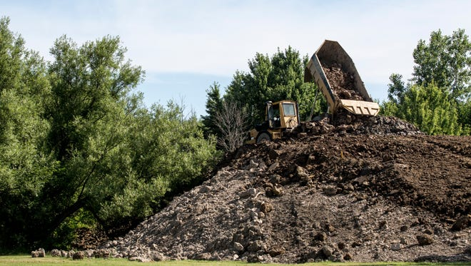 Contractors unload soil from a sewer project to build a sledding hill Friday, July 22, 2016 at Smiths Creek Community Park on Henry Street in Smiths Creek.