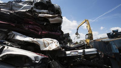 Crushed material, including junked cars, is stacked and ready to go in a shredder at Garden Street Iron & Metal in Fort Myers.
