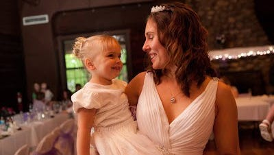 Space Coast Parent contributor Katie Parsons holds daughter Emilia, then 3, on Parsons' wedding day in 2011. Courtesy of Amy Straka Photography