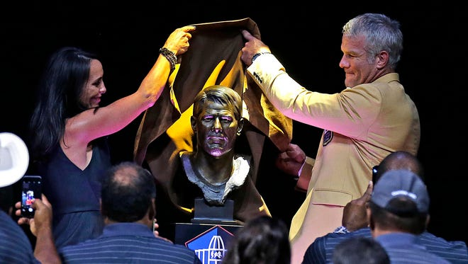 Aug 6, 2016; Canton, OH, USA; Former Green Bay Packers quarterback Brett Favre is introduced by his wife Deanna Favre (left) as his bust is unveiled  during the 2016 NFL Hall of Fame enshrinement at Tom Benson Hall of Fame Stadium. Mandatory Credit: Rick Wood/Milwaukee Journal Sentinel via USA TODAY Network