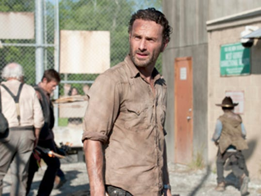 """In this publicity photo provided by AMC, actor, Andrew Lincoln, as Rick Grimes, center, is shown in a scene from AMC's """"The Walking Dead,"""" Season 3, Episode 1. (AP Photo/AMC, Gene Page)"""
