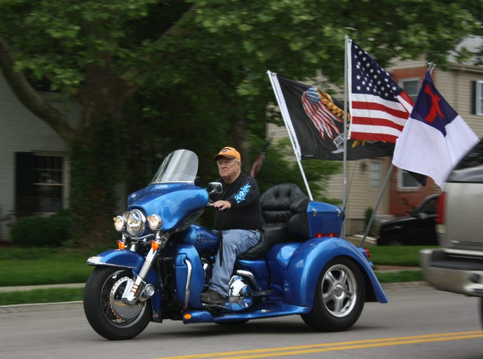 Flags flap in the wind on the back of a motorcycle driven by Larry Hamant of Bromley along South Fort Thomas Avenue for a Rolling Thunder POW-MIA remembrance ride Wednesday, May 21.
