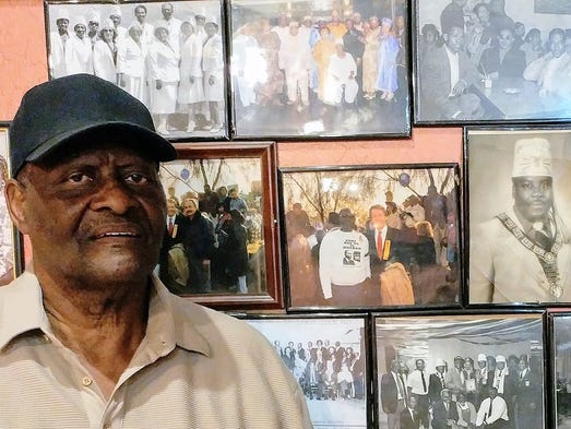 Art Whitmore stands beside photos, including some of