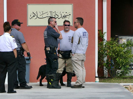 Officials from the Hillsborough County Sheriff's office, Fire Department and ATF talk outside the Daarus Salaam Mosque in Thonotosassa, Fla., after an arson there early Friday, Feb. 24, 2017. (James Borchuck/The Tampa Bay Times via AP)