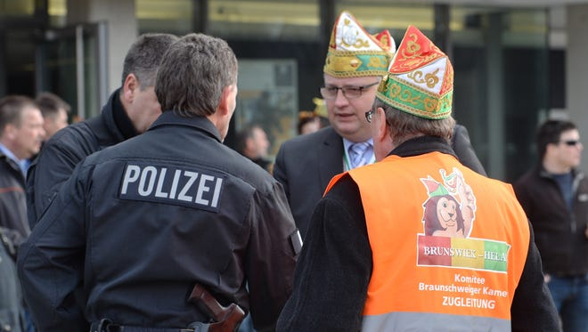 """Carnival parade organizers and police discuss in Braunschweig, Germany, Sunday, Feb. 15, 2015. Police in Braunschweig cancelled a popular carnival street parade because of fears of an imminent Islamist terror attack. Police spokesman Thomas Geese said police received credible information that there was a """"concrete threat of an attack"""" on Sunday's parade and therefore called on all visitors to stay at home. Braunschweig's carnival parade is the biggest one in northern Germany and draws around 250,000 visitors each year."""