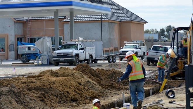 West Valley Construction workers working on the new ARCO AMPM project on Plaza Drive in Visalia.
