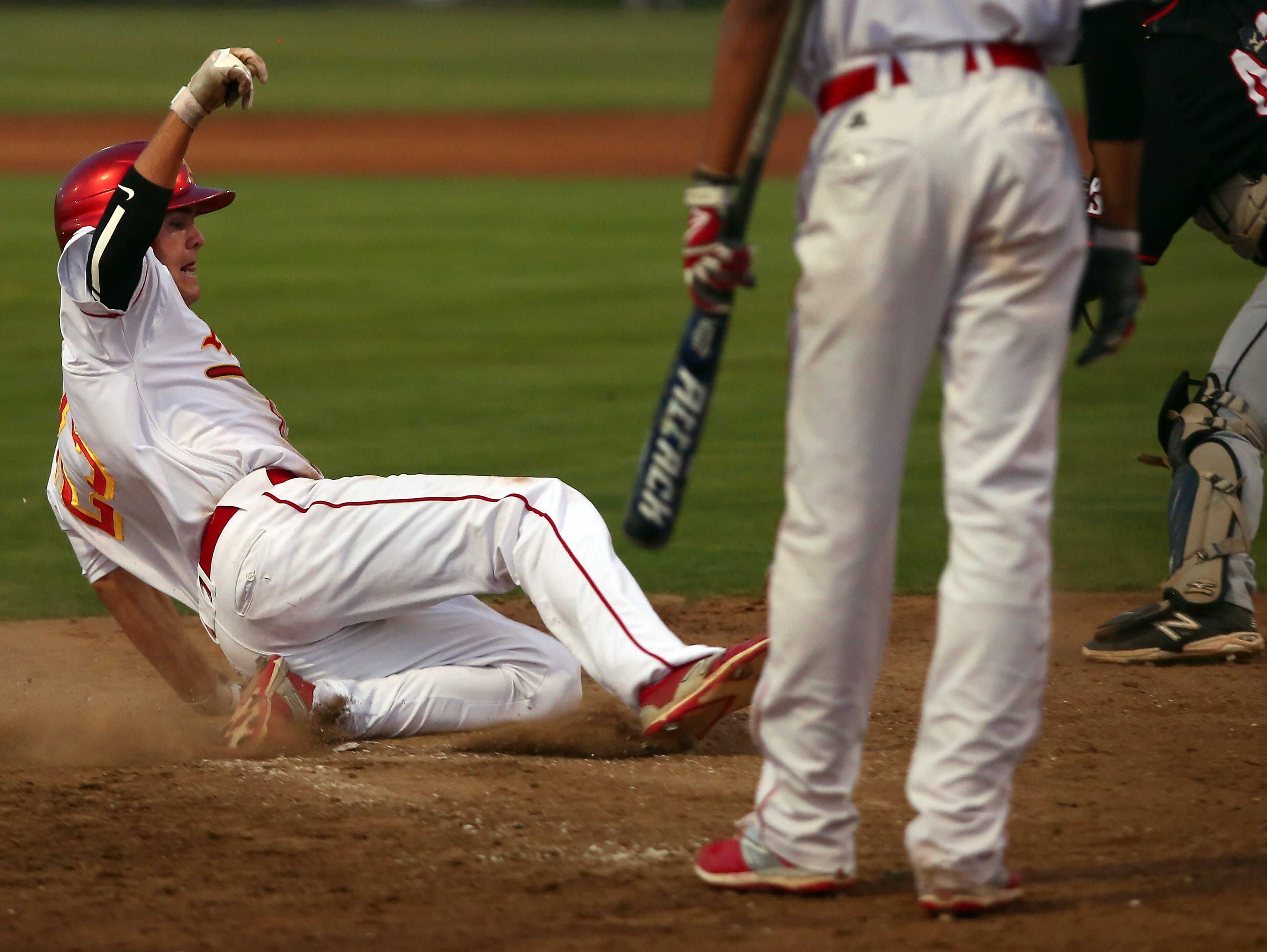 Palm Desert's Beau Berryhill (23) slides across home plate to score as the Aztecs host the Palm Springs Indians at home Tuesday, April 5, 2016.