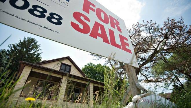 """A """"for sale"""" sign stands outside a home on Friday, June 7, 2013."""
