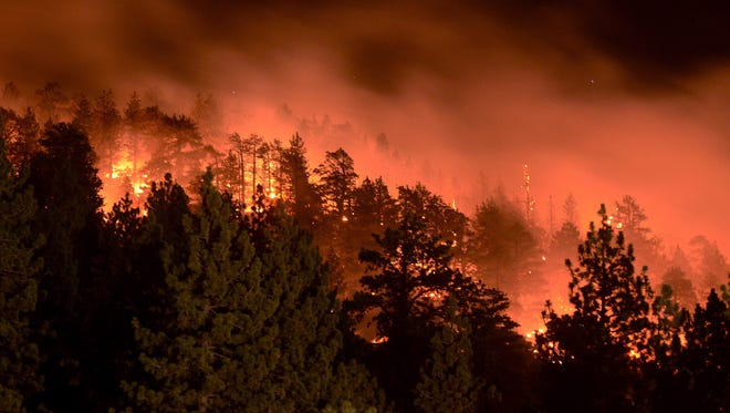 Flames from the Pine Fire burn in the back of trees on July 18, 2015, in Wrightwood, Calif.