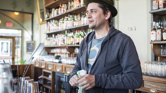 Charlie Hodge stands behind the bar at Sovereign Remedies