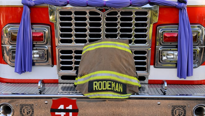 """Dennis Rodeman's firefighting gear sits on the front of a Lansing Fire Department engine Sept. 16,  before his funeral at the Breslin Center in East Lansing. Rodeman was killed when he was hit by a vehicle while collecting donations for the """"Fill the Boot"""" campaign."""