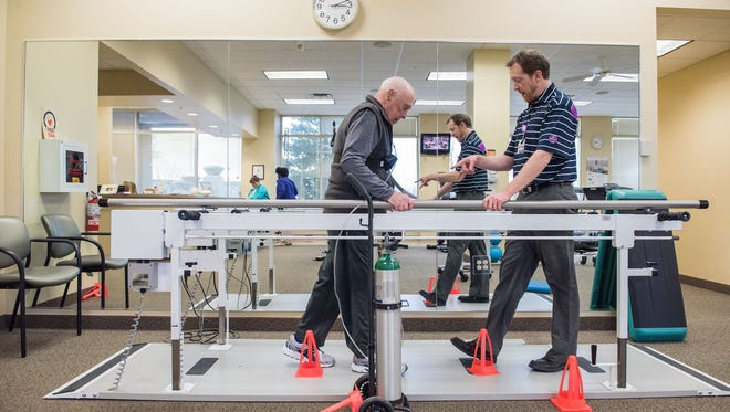 Allen Grubb works with Gordon Crouch, a physical therapist with KentuckyOne Health Frazier Rehab Institute at Springhurst Sports Medicine. He's recovering after an extended hospital stay to help with stability and balance by working at the parallel bars on walking and leg strength three times a week. Jan. 27, 2016