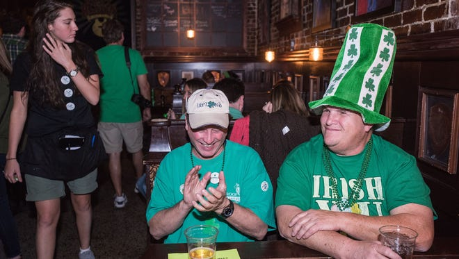 Woody Wood of Frankfort, Ky., left, and Peter Whetley watch people and the Indiana vs. Chattanooga NCAA game at O'Shea's Irish Pub during St. Patrick's Day festivities. March 17, 2016