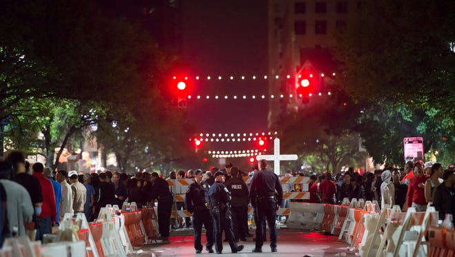 Hours before a shooting in downtown Austin, police keep an eye on the crowds from a cordoned-off section of 6th Street during SXSW.