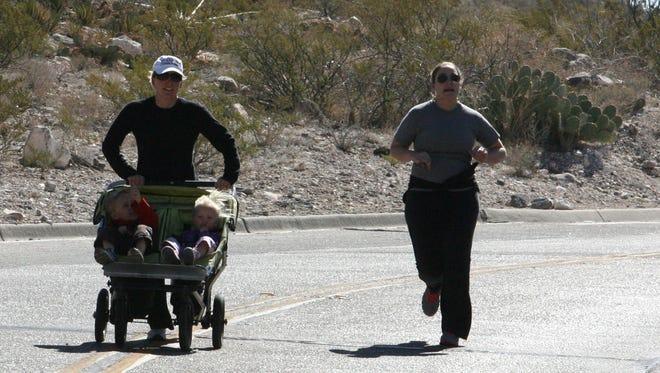 Kathy Revtyak, left, pushes her children on Scenic Drive with friend Erin Walton of Phoenix.