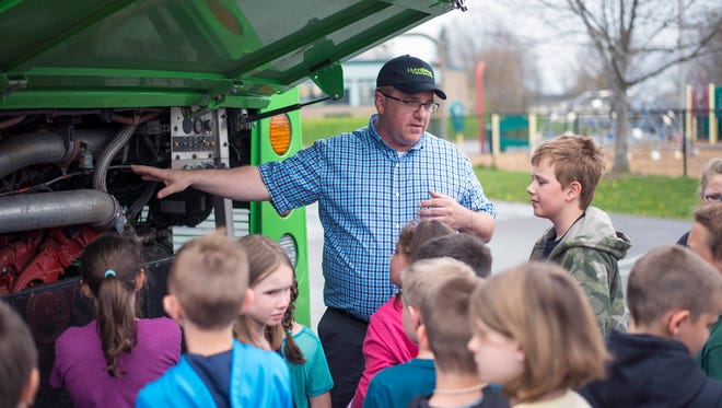 John Hroncich a business development manager at BAE Systems, talks to third grade students from Glenwood Elementary School about a hybrid bus designed by BAE on Friday.