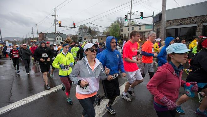Runners take off at the starting line of the Greater Binghamton Bridge Run half marathon in front of NYSEG Stadium in Binghamton on Sunday, May 1, 2016.