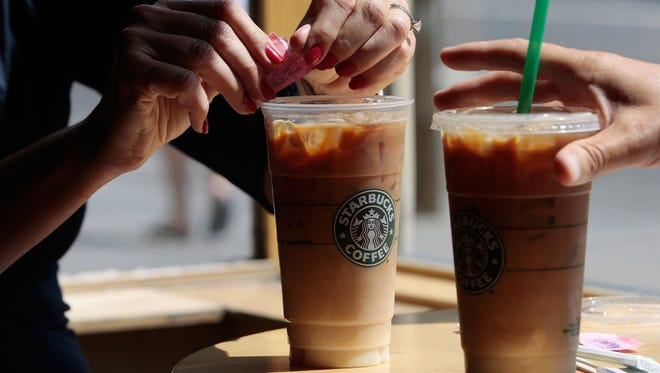 A couple has iced coffee drinks at a Starbucks Coffee shop in lower Manhattan August 21, 2009 in New York City.