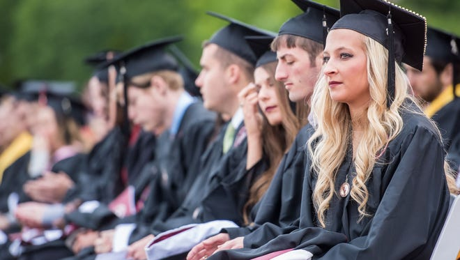 Charlie Knauer, 21, sits with graduates during the commencement address for Bellarmine University's 63rd annual commencement in the Owsley Brown Frazier Stadium on Clayton Field. May 14, 2016