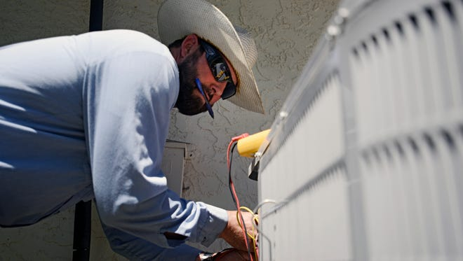 Josh Salow checks to see if an air conditioning unit is working at a home in Tempe, Ariz., on Thursday June 2, 2016. Salow said summer is the busiest season for AC repairs, and he fixes roughly three to four units a day in summer months. Parts of the Western U.S. are getting an early taste of scorching summer heat, forcing officials in California, Oregon and desert Southwest states to heed the warnings of dangerous, triple-digit temperatures in this first week of June.
