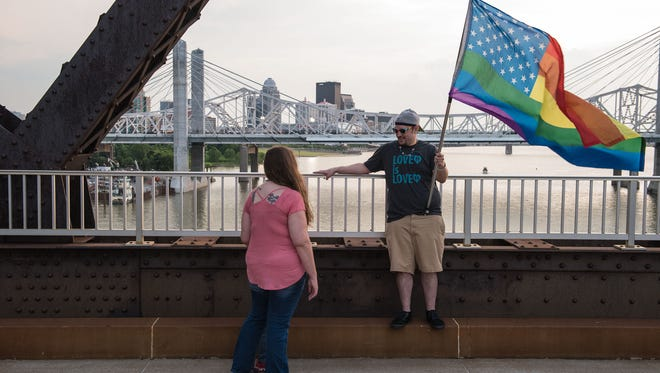 Valeria Bautista and her son Zaio, 5, talk with Christopher Heath about why they're with others mourning Sunday on the Big Four Bridge in downtown Louisville having a candlelight vigil for victims of the shooting at Pulse Nightclub, a LGBT bar in Orlando, Fla. June 12, 2016