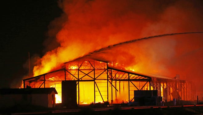Multiple agencies work to contain a fire at the Salt River Seed Company at 107th and Buckeye  Rd. Saturday, June 11, 2016 in Avondale, Ariz.