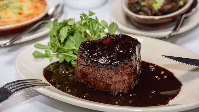 The Steak au Poivre, a black pepper crusted prime 12-ounce filet, served with brandy-green peppercorn sauce, as served at Z's Oyster Bar & Steakhouse. Served with the steak are the Au Gratin Potatoes, scalloped potatoes baked in cream with Gruyere cheese, left; and the Maker's Mushrooms, a ragout of oyster, shiitake, silver dollar and portobello mushrooms sautŽeed with garlic butter and Maker's Mark Kentucky bourbon. June 29, 2016