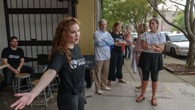 Tyler Alessi, left, looks on as Gabby Barker sings to accompaniment by Joe Mechavich on piano outside Royal's Hot Chicken as singers from the Kentucky Opera perform for the 5th Nulu Passport Party during the First Friday Trolley Hop at locations along Market Street. Aug. 5, 2016