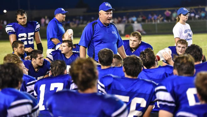 Mark Williamson, North Harrison Cougar head coach, addresses his team during the second half of Corydon at North Harrison High School in Ramsey, Ind. The North Harrison Cougars won the game 49 to 0. Aug. 26, 2016