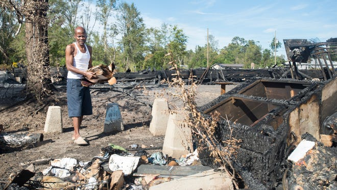 Elvin Mitchell tries to salvage photographs and other items from the shed behind his house in Century, FL on Monday, October 10, 2016.  Mitchell's shed and side of his house were damaged by the fire that burned down the Wesley Chapel Church next door on Sunday morning.