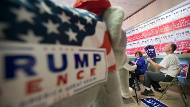 In prepartation for Donald Trump's Wednesday visit, Burt Dumas, right, and Linda Pierce assemble lawn signs at the Trump campaign office in Pensacola on Tuesday, November 1, 2016.