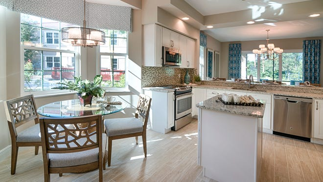 The Cortina I model's kitchen features GE stainless steel appliances and an island counter.