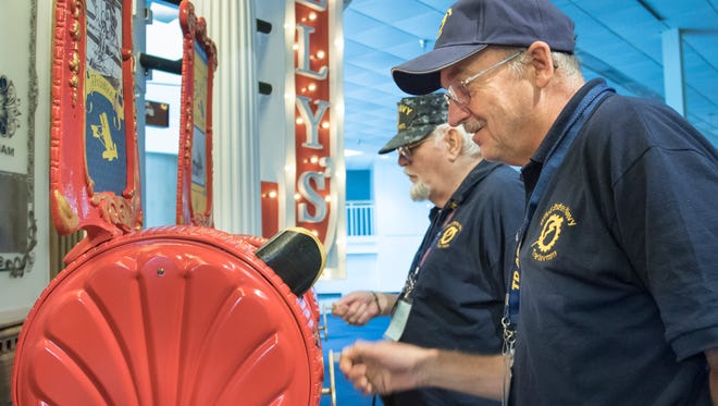 "Michael LeBlanc and Mike Goldman watch the short movies on the replica Mutoscope machines at the ""Dawn of Naval Aviation"" exhibit that is now open at the National Naval Aviation Museum in Pensacola on Thursday, November 10, 2016."